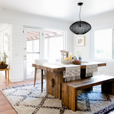 dining room with wood table, black pendant lamp, saltillo tile