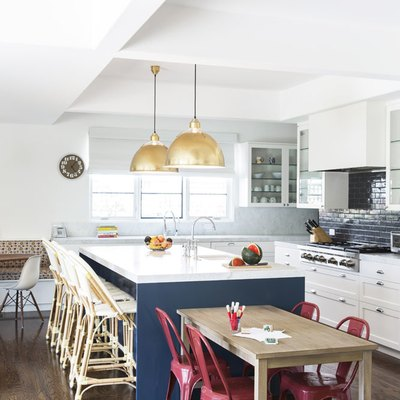 navy blue kitchen backsplash idea with dome shaped brass pendant lights over island