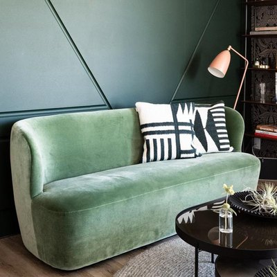 green sofa with pillows and a lamp nearby