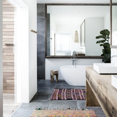 bathroom rug idea with two rugs and wood vanity topped by vessel sinks and freestanding bathtub
