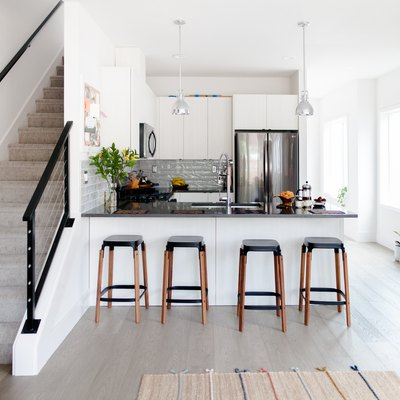 small kitchen with peninsula next to staircase