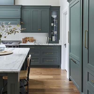 green kitchen cabinets with marble countertops and wood flooring