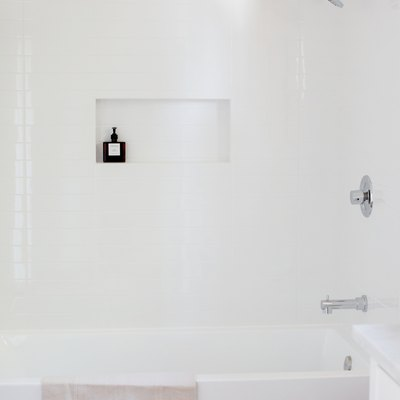 white tub with a fringed towel draped over, white shower wall