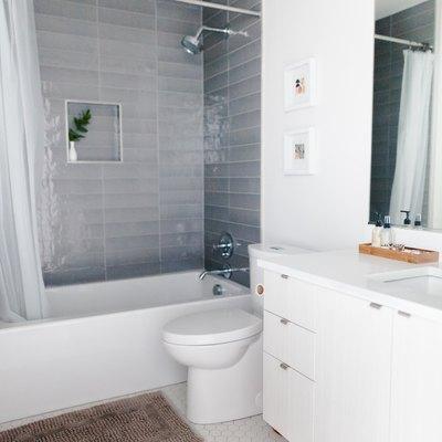 white hexagon floor tile, white bathroom vanity, white toilet, white tub with gray shower wall