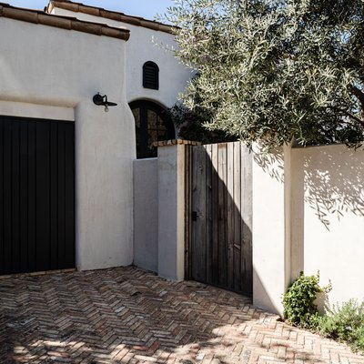brick driveway in a herringbone pattern by a Spanish-style home