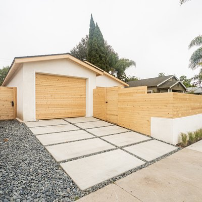 a concrete path surrounded by gravel, a light horizontal fence frames a garage