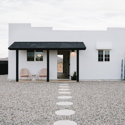 A stone path in the middle of a gravel walkway; a white southwestern-style home with a black awning