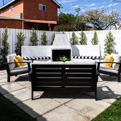 concrete paver patio, black patio furniture with white cushions, white privacy fence with small green trees evenly spaced apart