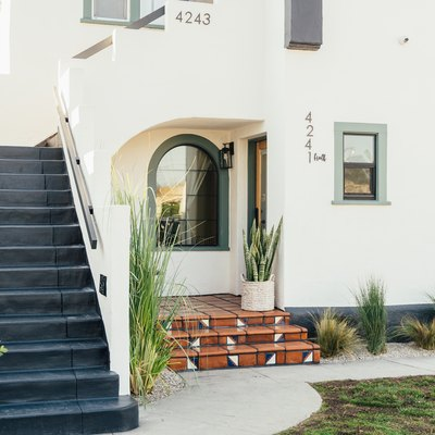 a white Spanish-style multi-family home with an exterior staircase, a curved window, a variety of green plants in a landscape bed with gravel