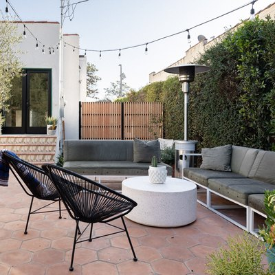 a backyard of a Spanish-style home with hexagon Terracotta pavers, two gray outdoor couches, two black patio chairs, a white, round coffee table, string lights, large privacy hedges