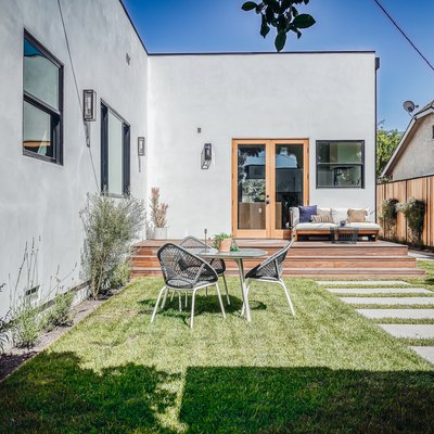 a gray house with a flat roof and a backyard with evenly spaced, modern concrete rectangular steps, various green plants and a table with three chairs