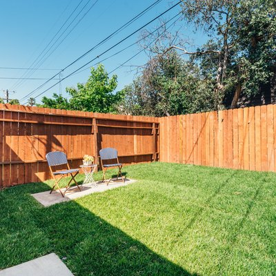 a freshly mowed green yard with two blue lawn chairs; a cedar fence surrounds the yard