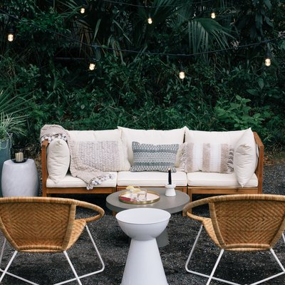 boho outdoor couch and two chairs, planters with poles that have string lights