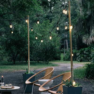 String lights on poles inside planters; two mid-century modern lawn chairs