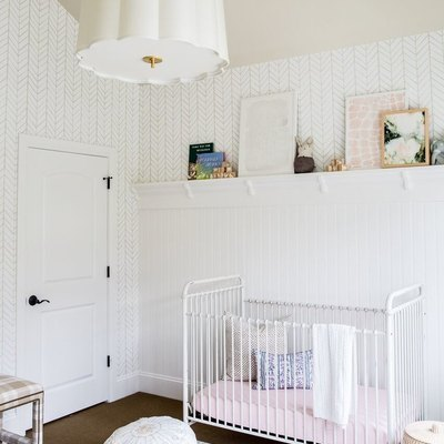 a white nursery with white crib and pendant light