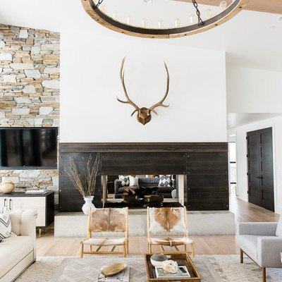 farmhouse living room with fireplace and stone accent wall with round chandelier