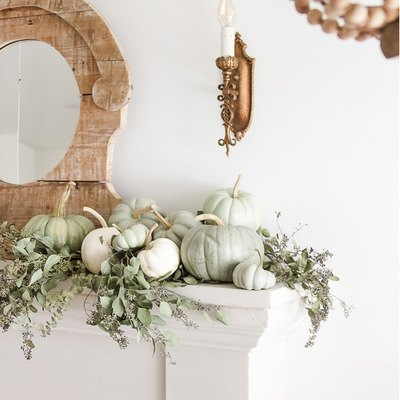 fall-inspired mantel decor with green and white heirloom pumpkins