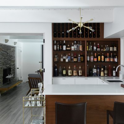 bar with cabinets full of bottles, white stone countertops, bar faucet and sink