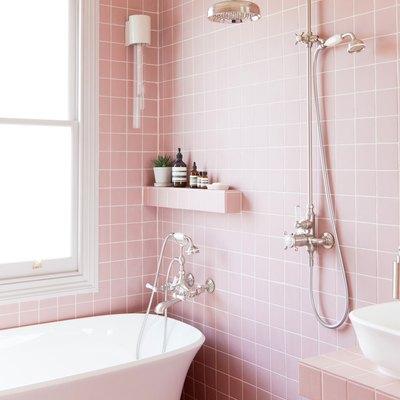pink bathroom with freestanding bathtub and exposed plumbing