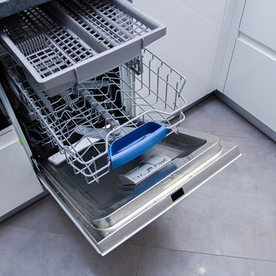 open modern dishwasher in the kitchen; built-in appliances in furniture.
