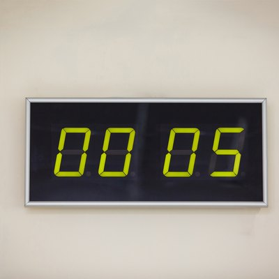 Black digital clock on a white background showing time hours minutes