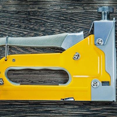 Building stapler gun on wooden board