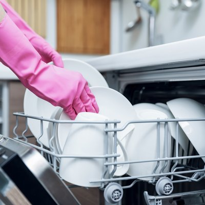 housewife taking out clean dishware from dishwasher at home kitchen