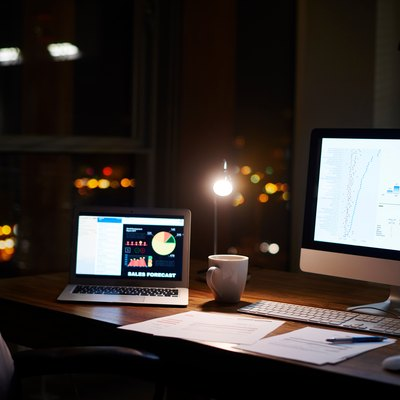 Laptop and computer on office desk at night