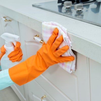 Woman cleaning the kitchen cabinet