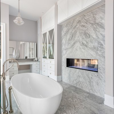Stunning master bathroom interior in luxury home with bathtub, shower, and fireplace.