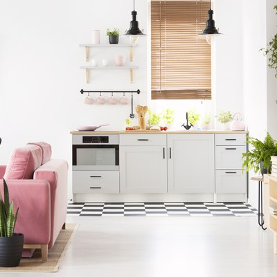 Real photo of open space kitchen interior with checkerboard floor, window with wooden blinds, pink velvet couch and many fresh plants