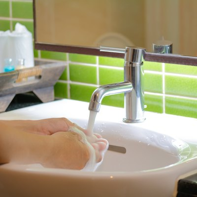 Close-Up Of Woman Washing Hands In Bathroom At Home