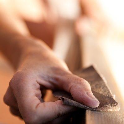 Hand of a woman sanding.