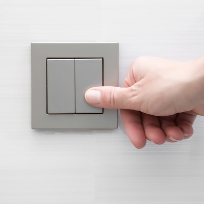 Woman's hand pressing light switch at the wall.