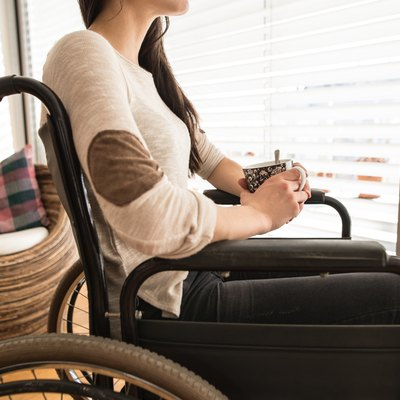 Unrecognizable young disabled woman in wheelchair at home.