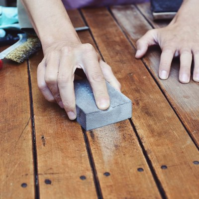 young man sanding a wooden table with a sanding block