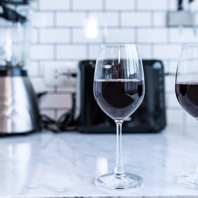 Red wine  in the glass In the modern kitchen . Classic white wall background .
