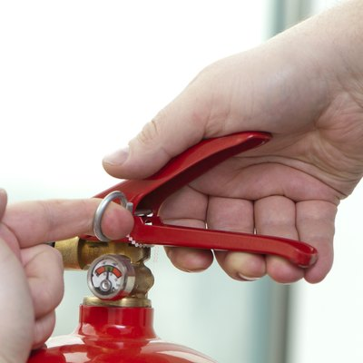 Hands pulling the pin to trigger of a fire extinguisher