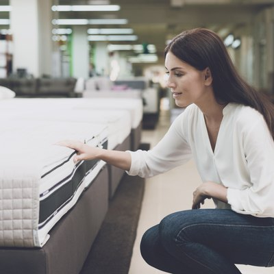 A woman chooses a mattress in a store. She sits next to him and examines him