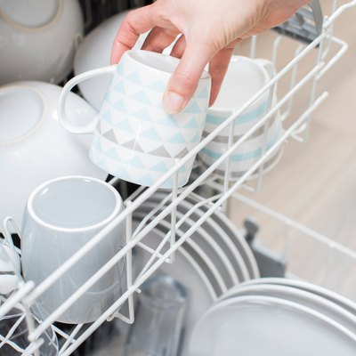 Close Up Of Woman Loading Crockery Into Dishwasher