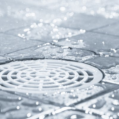 White plastic shower drain with drops of water around it