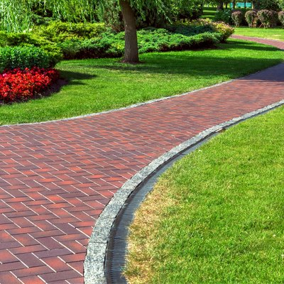 Red blocks footpath with drainage system in a park with green lawns and landscape design with bushes and red flowers.