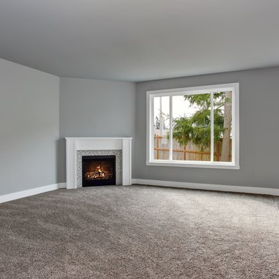 Grey house interior of living room with fireplace and carpet