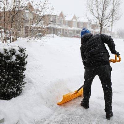 Man shoveling snow during snow storm in Toronto