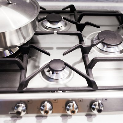 Modern stainless steel electric oven dial with frying pan closeup.