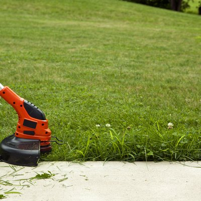 Using a string trimmer to cut longer grass and weeds at edge of pavement