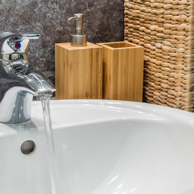 Bathroom sink with soap dispenser and toothbrushes container