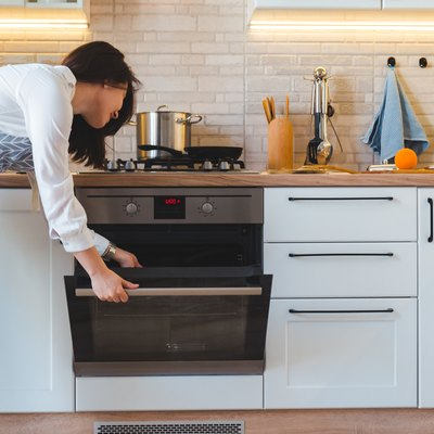 young pretty woman open oven to cook. domestic kitchen concept