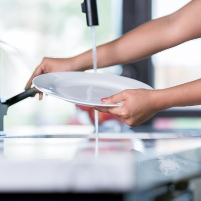 Young woman rinses plate while standing at kitchen sink and washing dishes