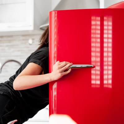 Woman looking for food in refrigerator in modern bright apartments.